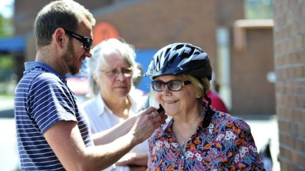 "Carol Walker of Kingston has a helmet fitted by Pedal Power project manager, Stuart Jones during Pedal Power ACT's ""Come ..."