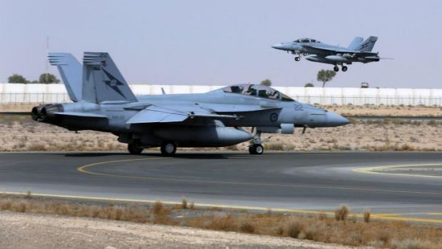 All on: A Royal Australian Air Force  F/A-18F Super Hornet takes off as another taxis along the runway as they start ...
