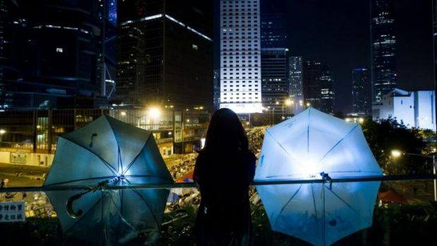 A woman stands between two umbrellas as she looks over the bridge to Admiralty district in Hong Kong.