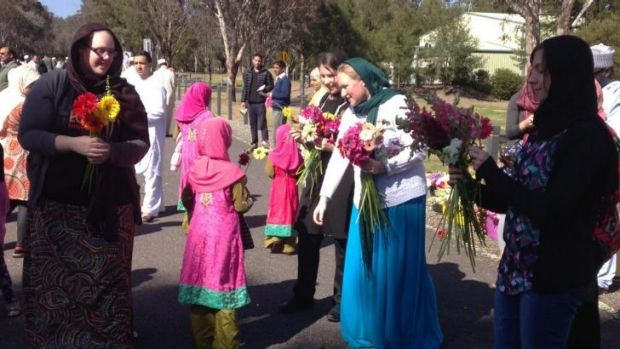 Floral gesture: Ten Canberran women hand out flowers to the ACT Islamic community in Bruce on Saturday