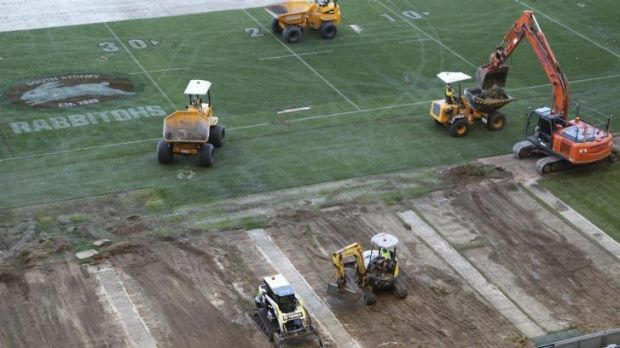 Patchwork: Diggers begin ripping up the turf at ANZ Stadium on Tuesday.
