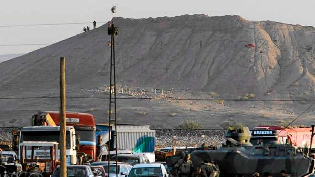 Turkish forces patrol the border as militants with the Islamic State group are seen after placing their group's flag on ...
