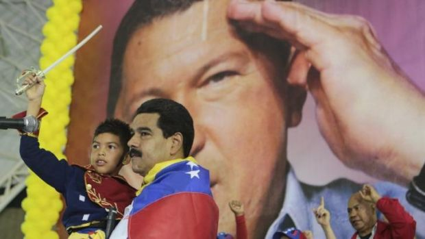 Venezuela's President Nicolas Maduro carries a child dressed up as national hero Simon Bolivar in front of a poster of ...