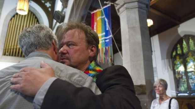 Reverend Schaefer hugs a supporter after his reinstatement in June.
