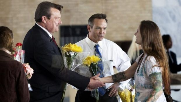Larissa Boose Williams, right, and her daughter Sedona, 10, hand out flowers to Tony London, left, and Tim Bostic after ...