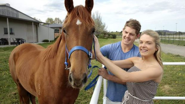 NSW batsman Daniel Hughes with his partner Erin Molan at Nick Olive's stables at Thoroughbred Park where their ...