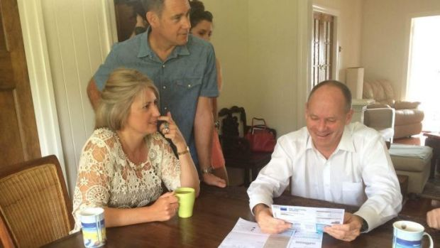 Gordon Park couple Amy Ward and Todd Winks go over their power bills with Premier Lord Mayor Campbell Newman on Sunday ...