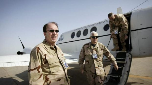 Money man: Stuart Bowen, left, and two aides get off a plane in the Iraqi city of Nasiriya in May 2006.