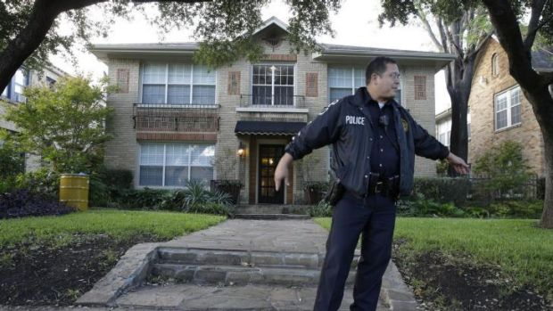 On guard: A policeman stands watch outside the home of the hospital worker infected with Ebola in Texas and a yellow ...
