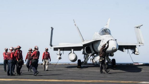 Ground crew on a US aircraft carrier prepare a fighter jet for take-off. Turkey has approved take-offs from bases close ...