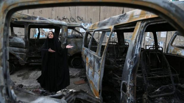 A woman reacts to the carnage at the site of a car bomb attack in the Shula neighborhood of Baghdad.