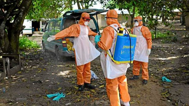 Members of a burial team spray themselves with chlorine after removing the body of a suspected Ebola victim from a home ...