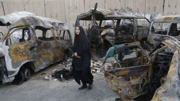 Charred wrecks: A woman walks among vehicles destroyed in a car bomb attack in Baghdad.