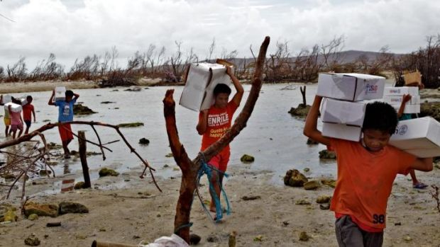 Locals carry aid packages after Cyclone Haiyan.