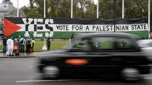 Support: A London taxi drives by as pro-Palestinian supporters position a giant banner calling for a recognised ...