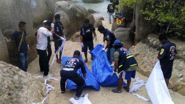 Thai police officers with the bodies of two British tourists found murdered on a Koh Tao beach.