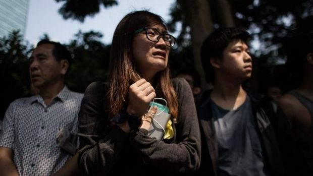 A pro-democracy protester reacts while watching police remove barricades on Queensway in the city's Admiralty district ...