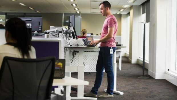 PwC consultant Tom Simmonds using a standup desk. No one now has an individual space that is theirs.
