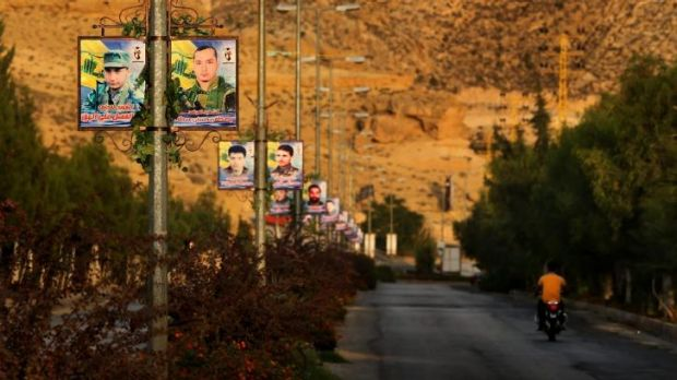 Overrun: Posters of dozens of Hezbollah fighters killed fighting in Syria against IS line the road entering Hermel ...