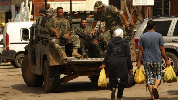 Community: A man and a woman walk past Lebanese fighters in the village of Al-Labweh in the Bekaa Valley.