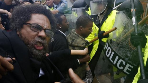 Rough treatment: Activist Cornel West is knocked over during a scuffle with police during a protest at the Ferguson ...