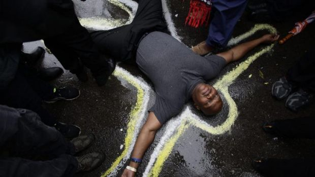 Stark message: Pastor Charles Burton has his body outlined with chalk to replicate a crime scene as he and other ...