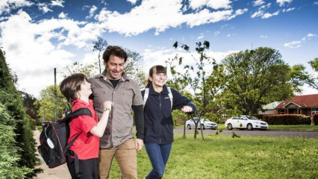 Doing it together: Robin, 10, and Finn Burton, 13,  give dad Anthony a hurry up as they walk home from school in Ainslie.