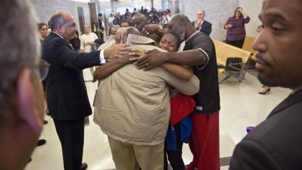 Powerful: David McCallum, centre, is embraced by his immediate family after his exoneration on Wednesday.