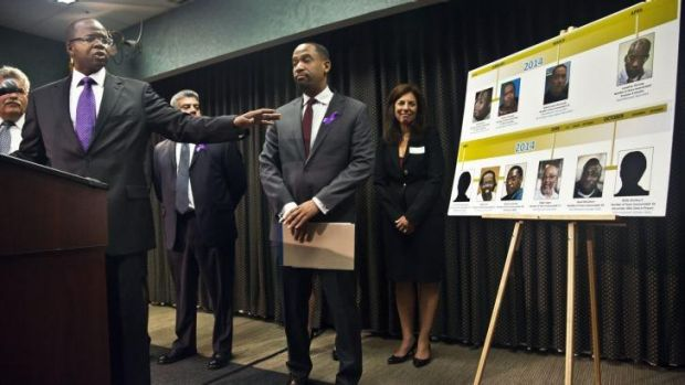 Nine and counting: Brooklyn District Attorney Ken Thompson, left, points to a time-line photo display of individuals ...