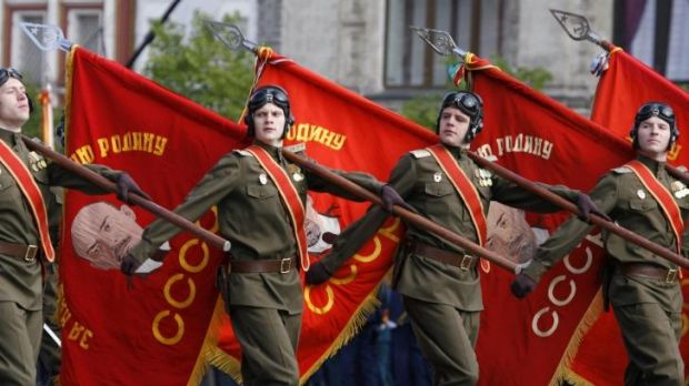 Soldiers march carrying flags displaying portraits of the Soviet state founder, Vladimir Lenin, at Red Square in Moscow ...