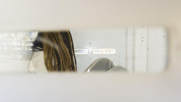 Charged: The 23-year-old woman arrives at court in the back of a police van.