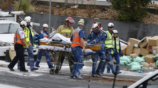Rescue workers carry away one of the people trapped under the truck.