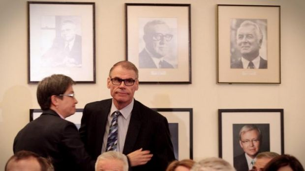 Senator John Faulkner is embraced by Senator Penny Wong beneath a portrait of former Prime Minister Gough Whitlam in the ...