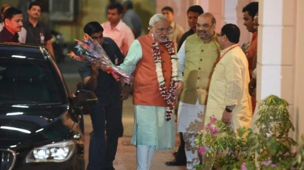 On his way: Indian Prime Minister Narendra Modi (in orange) arrives at the headquarters of the ruling BJP in Delhi on ...