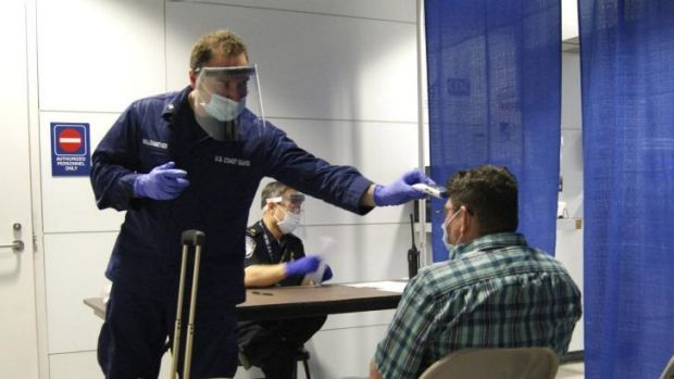 US Coast Guard and Customs officials conduct pre-screening measures on a passenger arriving from Sierra Leone at ...