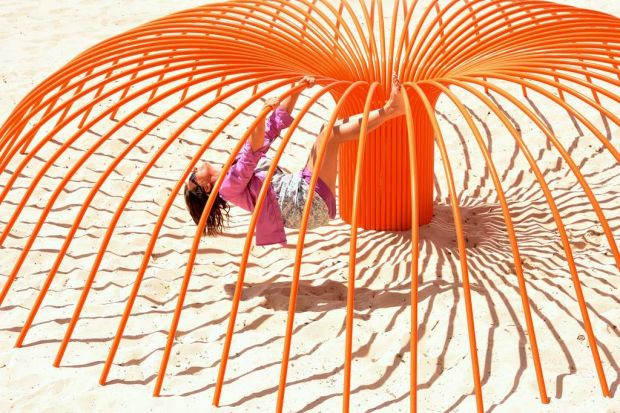 """Rebecca Rose playing in her sculpture titled """"Sea anemone"""""""