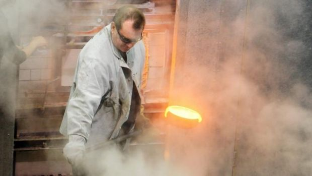Hot work: Canberra Glassworks technical manager Tom Rowney removes the excess glass from the tank furnace.
