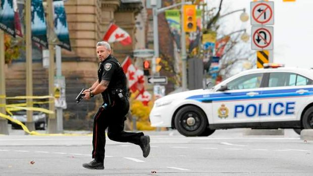 An Ottawa police officer runs with his weapon drawn outside Parliament Hill in Ottawa.