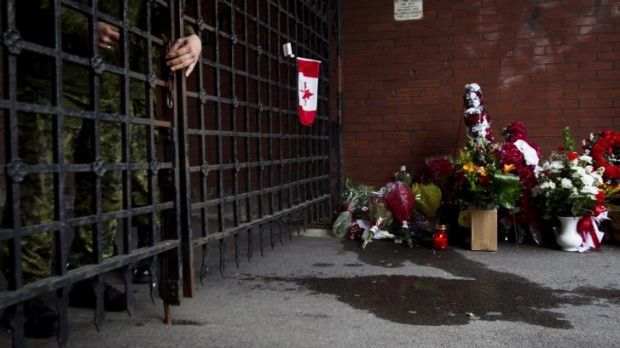 A soldier locks the gates as flowers are placed at a memorial outside the gates of the John Weir Foote Armory.