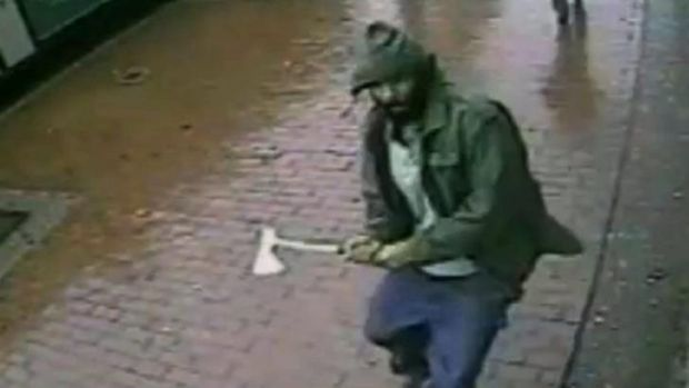 An unidentified man approaches New York City police officers with a hatchet in the Queens borough of New York in image ...