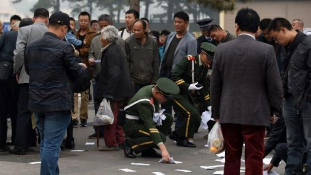 Rule of law: Chinese police pick up the protest leaflets thrown by the woman and two other women. The Communist Party is ...