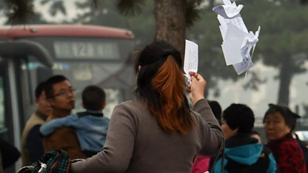 Public anger: A woman throws protest leaflets at an entrance to Tiananmen Square during the Communist Party's Fourth ...