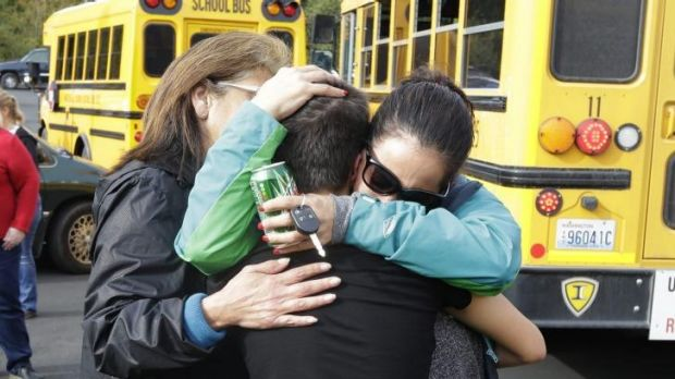Parents embrace in front of school buses after the shooting at Marysville Pilchuck High School.