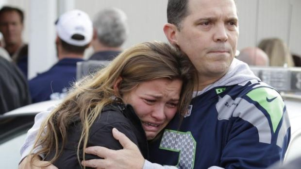 People react as they wait at a church, where students were taken to be reunited with parents following a shooting at ...
