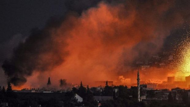 Under fire: Smoke and flames rise following an explosion in the Syrian town of Kobane.