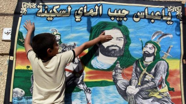 Holy days: An Iraqi child touches a banner bearing the portraits of Imam Hussein and his brother Abbas, both revered by ...