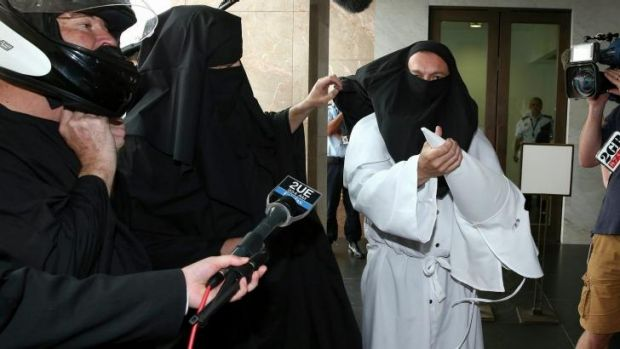 Protester Sergio Redegalli removes a Ku Klux Klan mask to reveal he is wearing a burqa underneath.