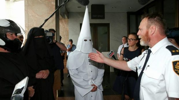 Security turn away protesters with facial coverings from Parliament House.
