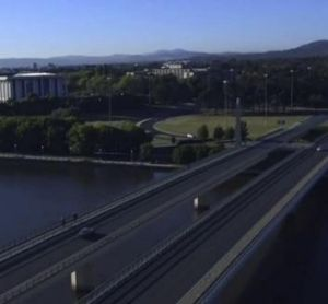 The opening shot of Canberra in Episode 1 of <i>The Code</i>: An aerial view of a car crossing Commonwealth Avenue ...