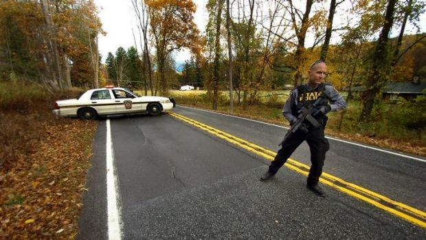 A Pennsylvania State Trooper patrols along a closed section of Lower Swiftwater Road during a massive manhunt for killer ...